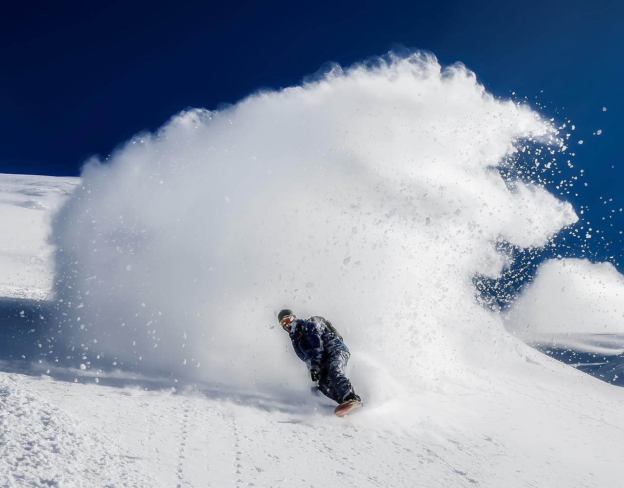 Snowboarder effectuant un virage dans la poudreuse