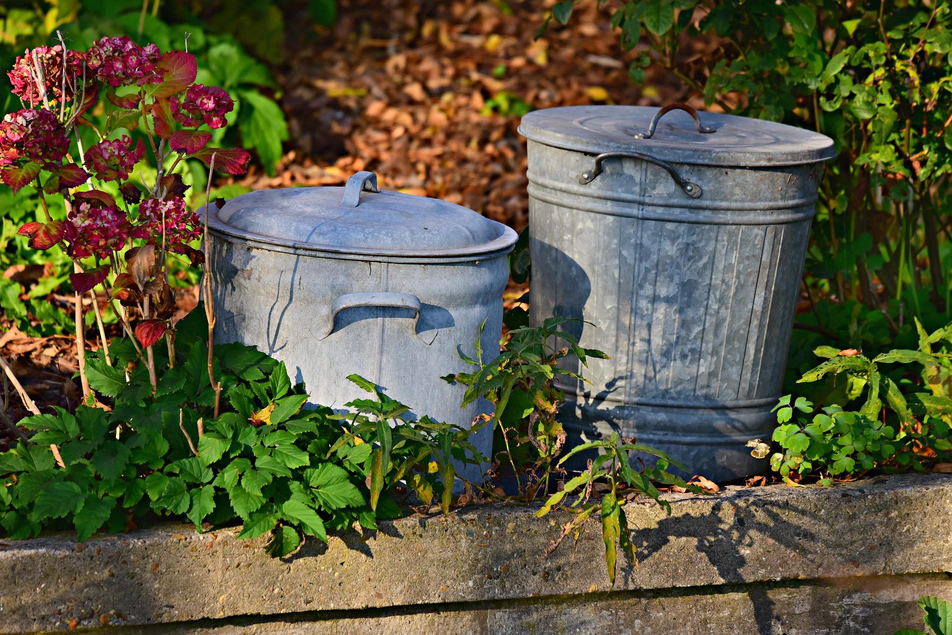 deux poubelles en metal dans un jardin